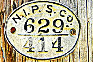 An old NIPSCO sign on a utility pole.